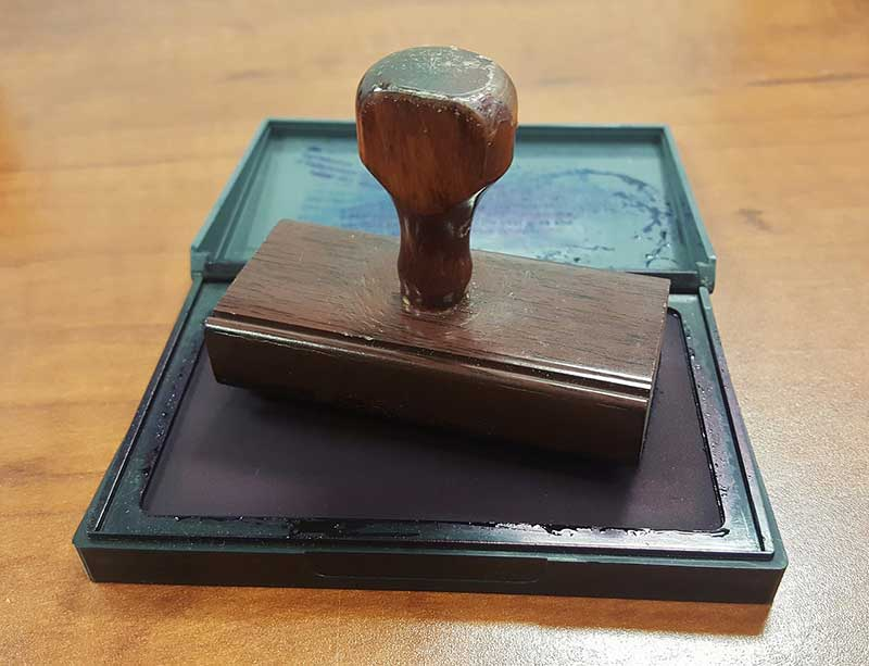rubber stamp on top of a wooden table