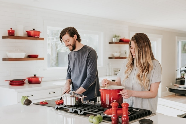 man and woman smiling while cooking